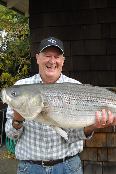 Innkeeper is wearing a blue plaid shirt and holding a 40 pound striped bass