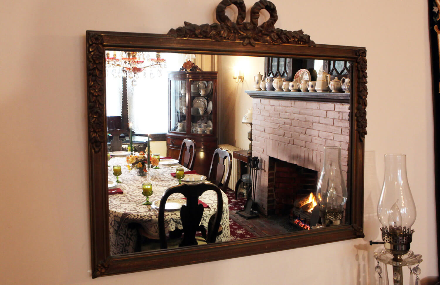 brown rectangular antique mirror reflects the Dining Room table and mauve fireplace