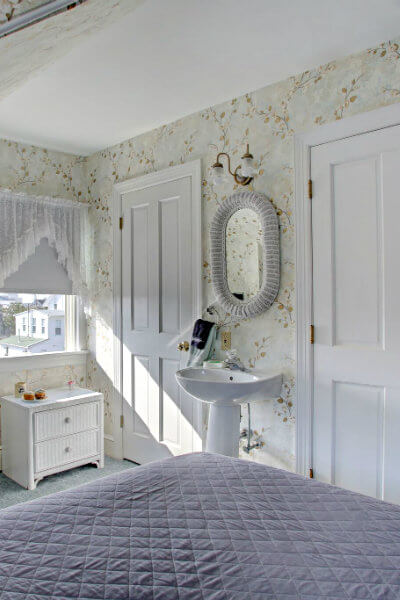 white pedestal sink, white wicker vanity and chair and tall dresser with TV