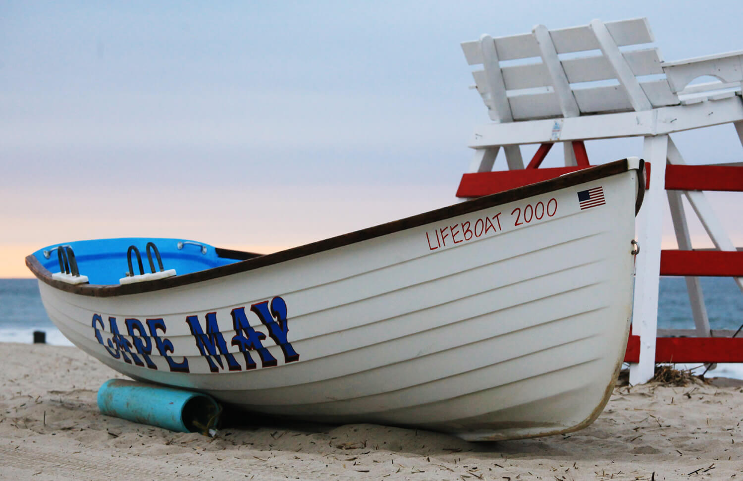 red and white lifeguard chair and white boat on the sandy beach