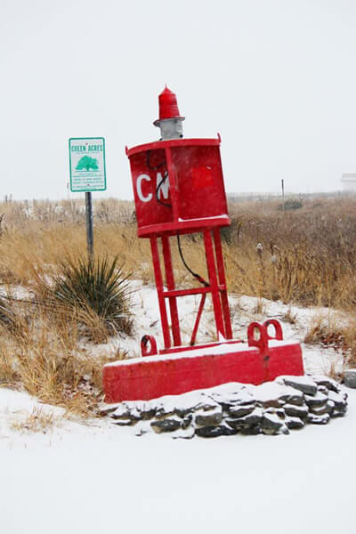 "red buoy with white ""CM"" sitting on the brown and tan dunes"