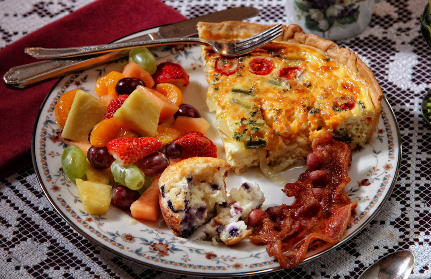 wedge of ham and cheese quiche, blueberry muffin, bacon and red strawberries, orange/ green melon, red/ green grapes
