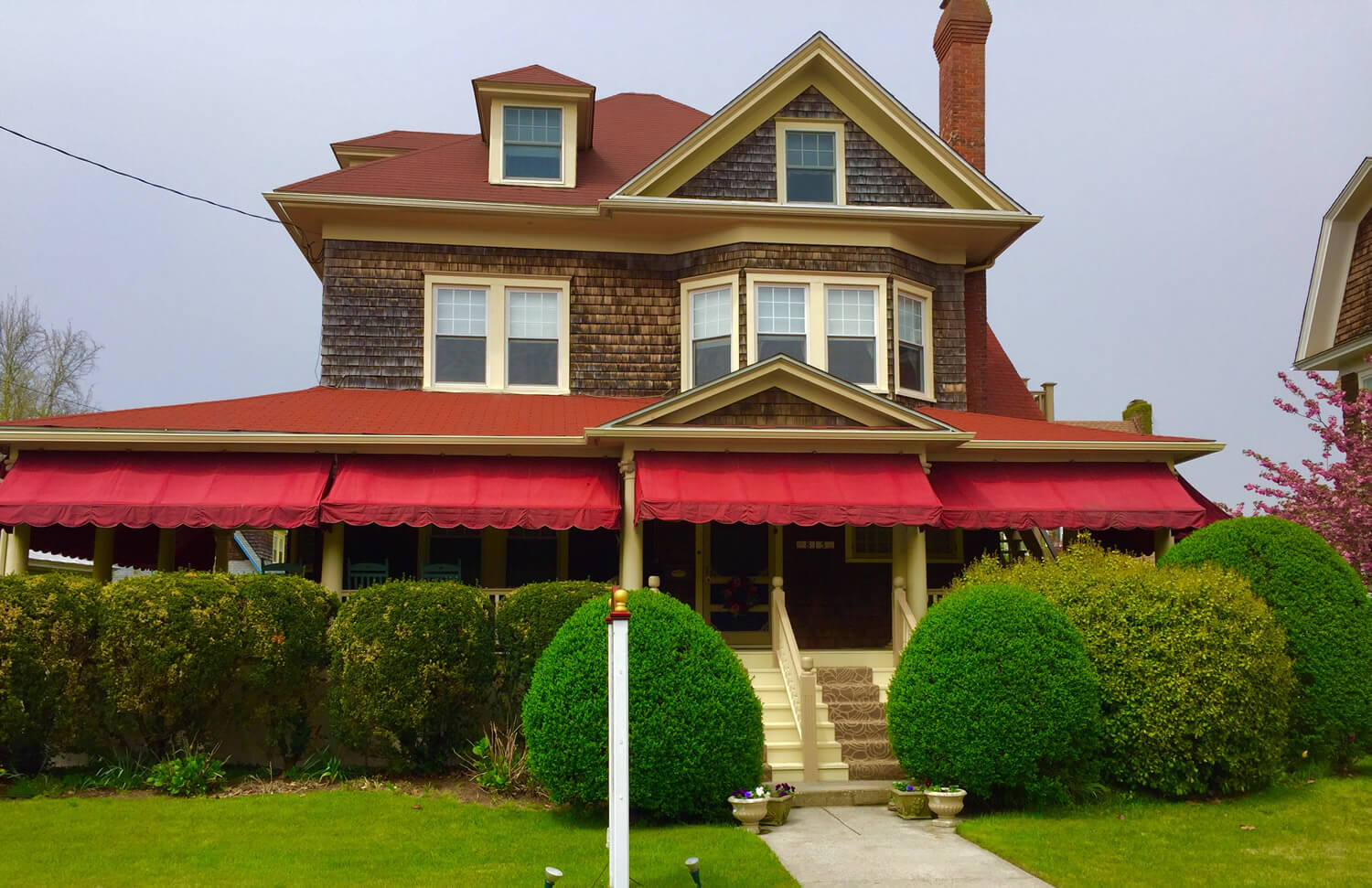 Inn with red awnings and brown cedar shakes and greenery