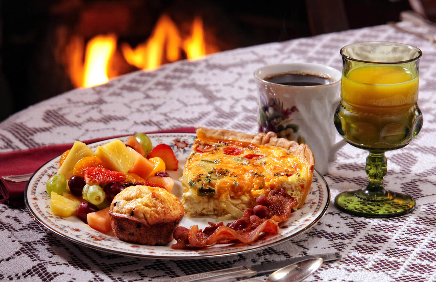 Vegetable Quiche with blueberry muffin, bacon and fresh fruit accompanied by black coffee and orange juice
