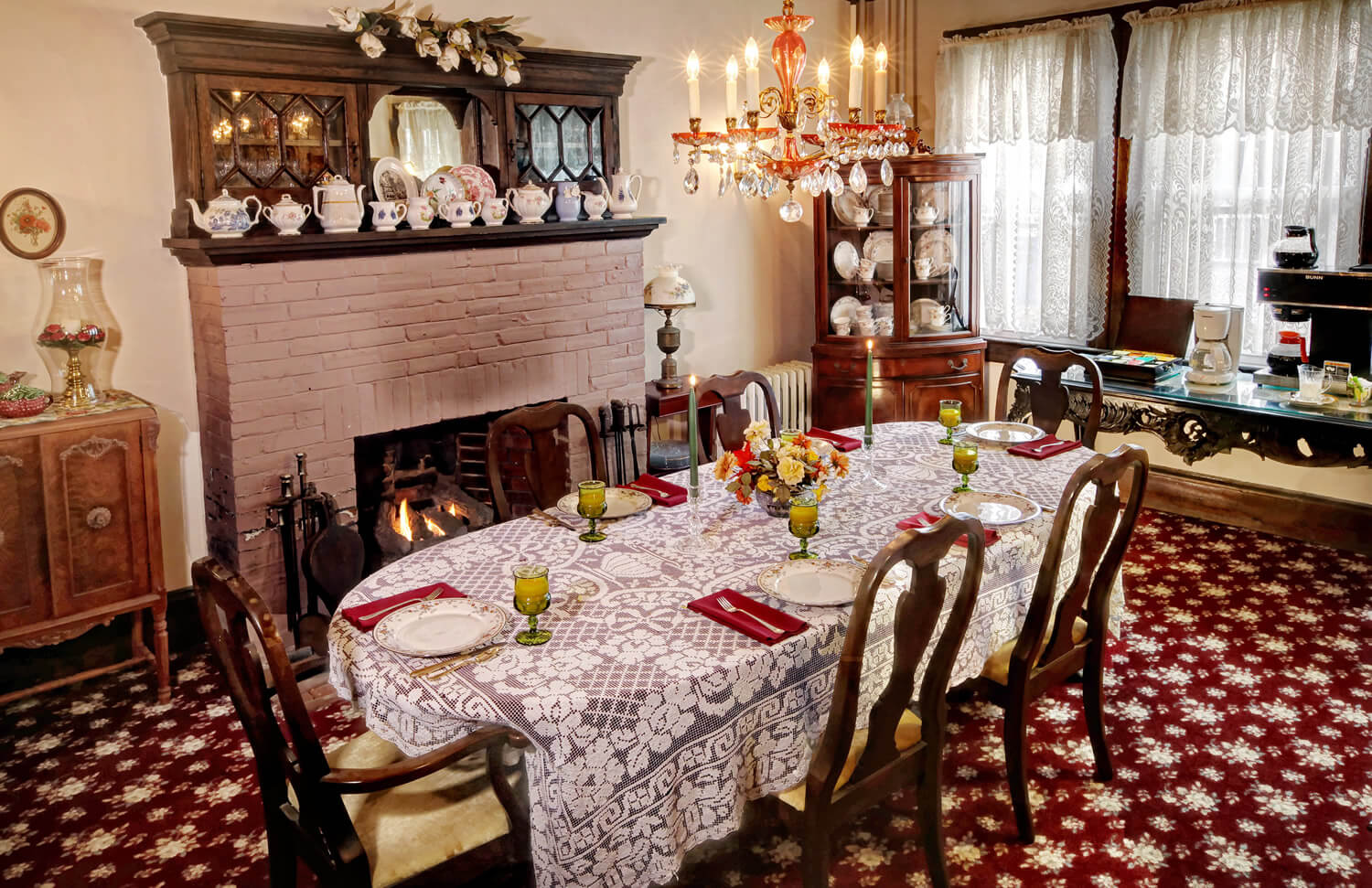 Cherry wood dining room table and mauve fireplace with silk flower centerpiece
