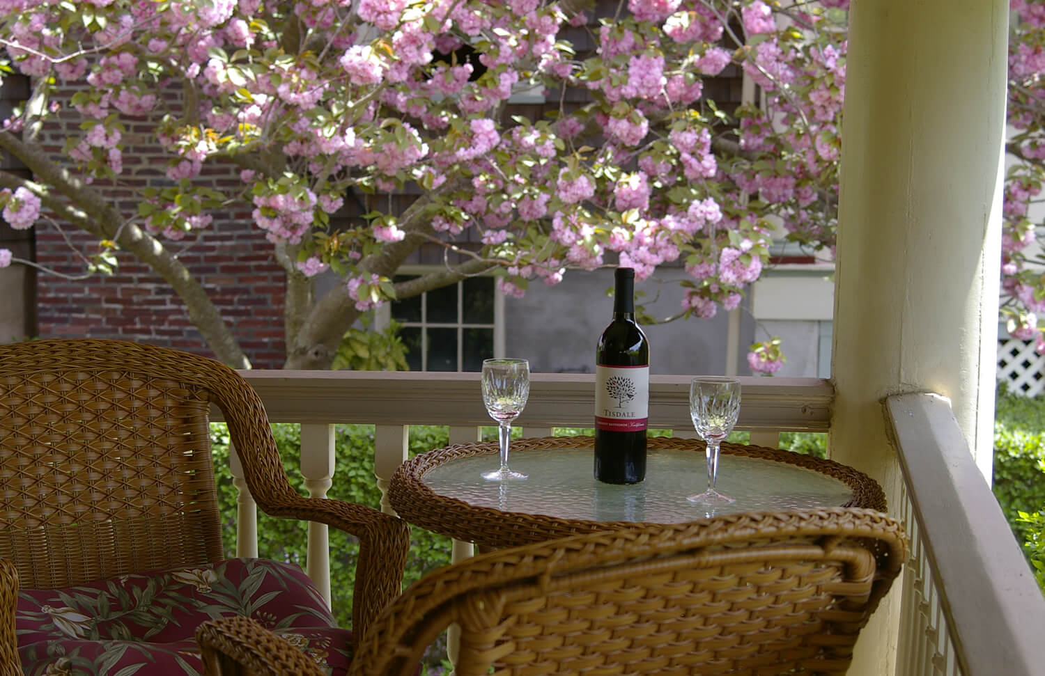 Exterior porch table with 2 wineglasses and a bottle of red wine with an ornamental flowering tree