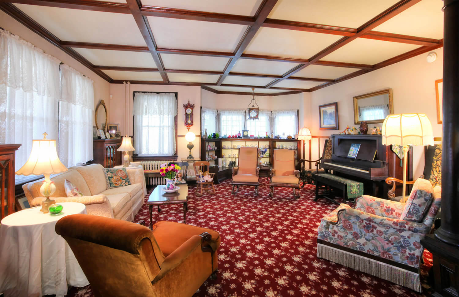 antique-filled living room with maroon floral carpet, piano, beige couch, and 2 armchairs