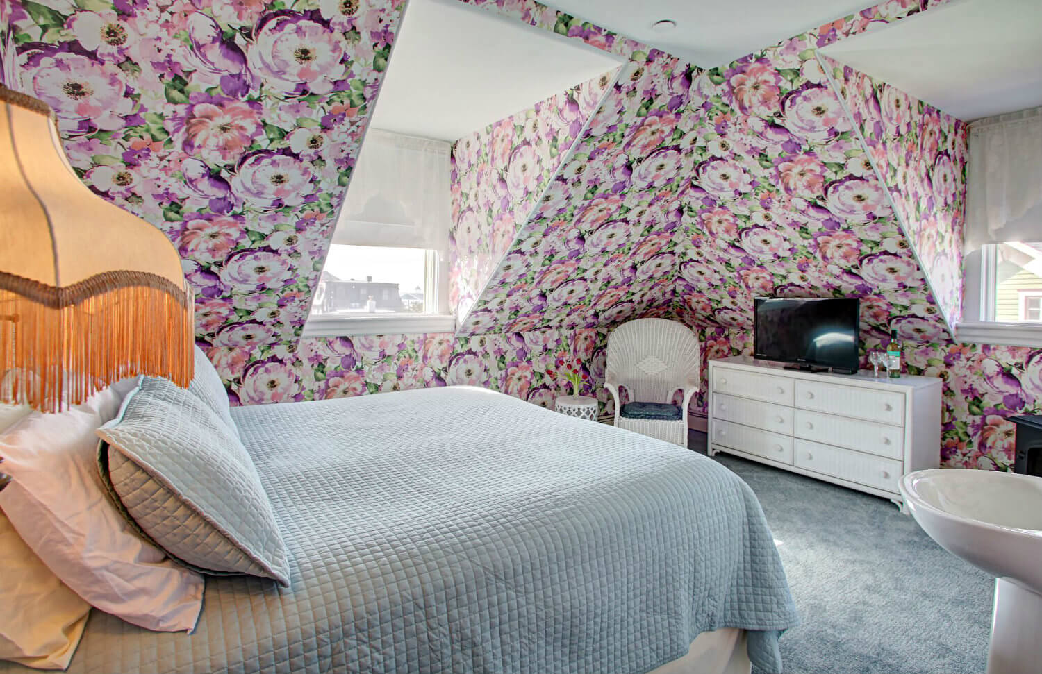 king bed with beige floral quilt and multi-colored hydrangea wallpaper, corner fireplace and TV sitting on white wicker dresser