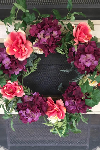 wreath with pink roses and purple hydrangeas hanging on front beige door