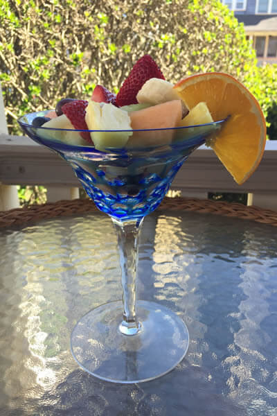 fresh fruit salad in a large blue martini glass with a slice of orange garnish