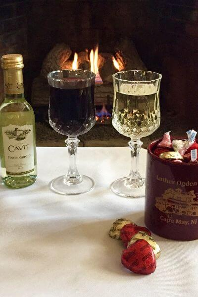 Red and white wine glasses with gold and red chocolates in front of a fireplace